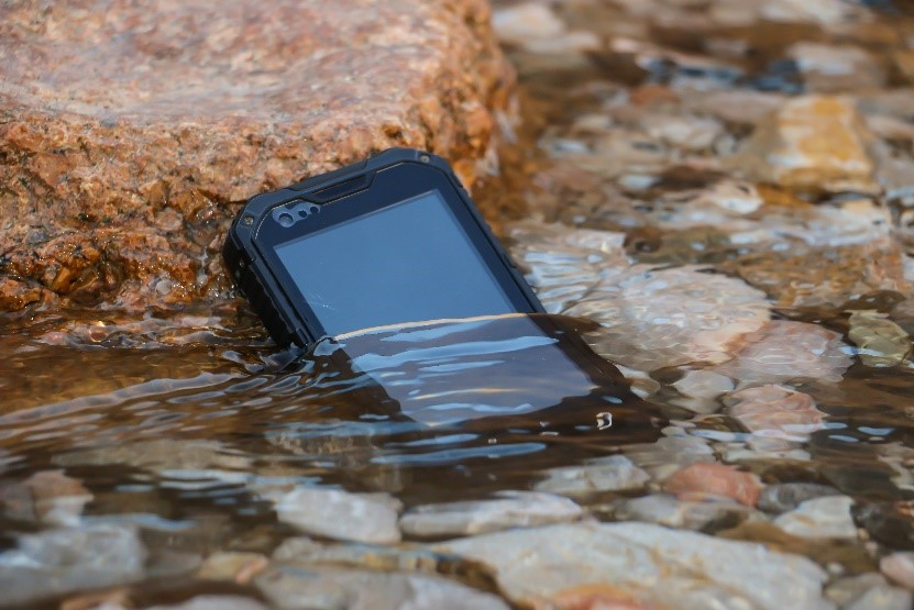 A rugged tablet half submerged in a stream of water